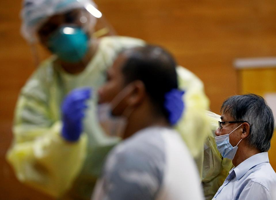 Essential workers have their noses swabbed before returning to the workforce at a regional screening center, amid the coronavirus disease (COVID-19) outbreak in Singapore June 10, 2020.   REUTERS/Edgar Su
