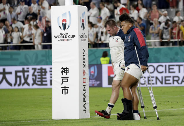 United States' David Ainuu walks on crutches across the field following their Rugby World Cup Pool C game at Kobe Misaki Stadium, between England and the United States in Kobe, Japan, Thursday, Sept. 26, 2019. (AP Photo/Aaron Favila)