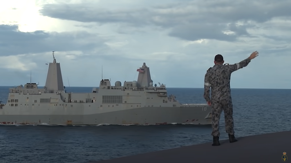 An Australian soldier waves to a US navy ship during a joint exercise in the Pacific