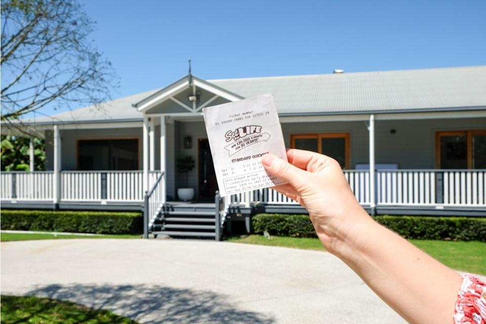 lottery player holds set for life ticket in front of house