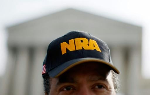 A gun rights advocated with a cap bearing the initials of the National Rifle Association stands outside the Supreme Court in 2008