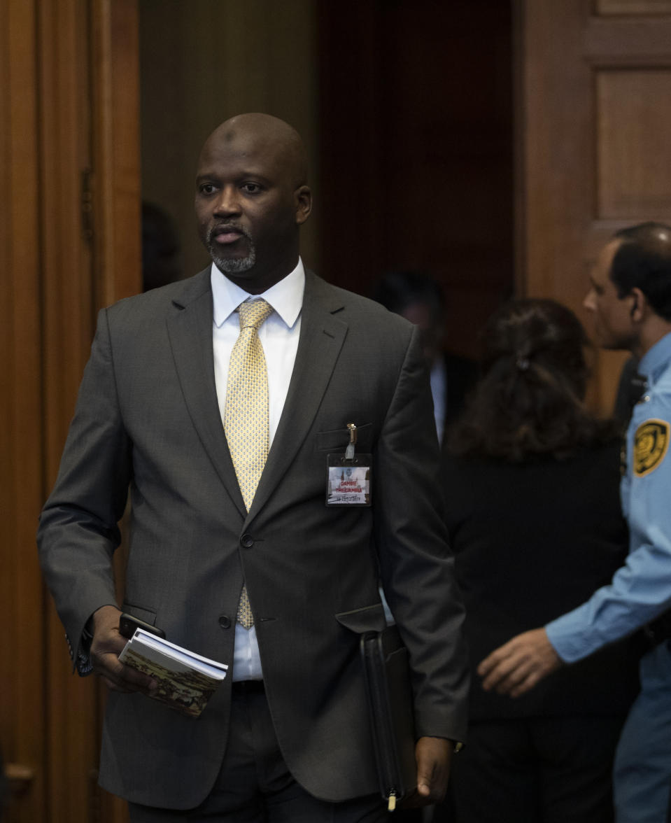 Gambia's Justice Minister Aboubacarr Tambadou enters the court room where Myanmar's leader Aung San Suu Kyi addressed judges of the International Court of Justice on the second day of three days of hearings in The Hague, Netherlands, Wednesday, Dec. 11, 2019. Aung San Suu Kyi will represent Myanmar in a case filed by Gambia at the ICJ, the United Nations' highest court, accusing Myanmar of genocide in its campaign against the Rohingya Muslim minority. (AP Photo/Peter Dejong)
