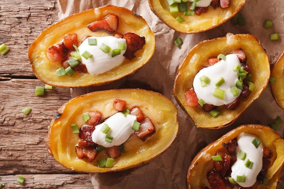 "This version of the classic bar snack gets Monterey Jack cheese and sharp cheddar, plus crispy bacon, green onions, and sour cream, but you can also go rogue with the toppings and dress your potato skins any way you like. <a href=""https://www.epicurious.com/recipes/food/views/potato-skins-with-bacon-and-cheese-103866?mbid=synd_yahoo_rss"" rel=""nofollow noopener"" target=""_blank"" data-ylk=""slk:See recipe."" class=""link rapid-noclick-resp"">See recipe.</a>"
