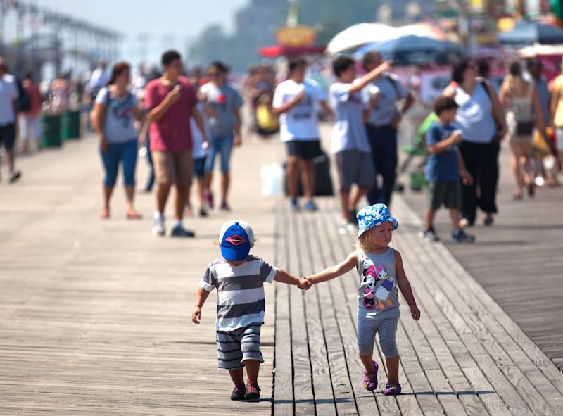 FILE - In this Aug. 26, 2011, file photo, children stroll along the boardwalk that connects Brighton Beach with Coney Island, in the Brooklyn borough of New York. A hearing is taking place in New York City Monday, March 12, 2012 on a planned makeover for stretches of the aging, 2.7-mile boardwalk that would include replacing it with a combination of plastic and concrete.(AP Photo/John Minchillo, File)