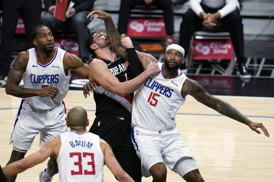 Los Angeles Clippers center DeMarcus Cousins (15) works for position under the basket next to Portland Trail Blazers center Enes Kanter, center, and Clippers' Kawhi Leonard, left, during the first half of an NBA basketball game Tuesday, April 6, 2021, in Los Angeles. (AP Photo/Marcio Jose Sanchez)