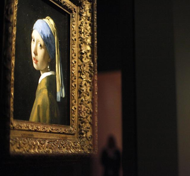 """FILE - This June 19, 2013 file photo shows Johannes Vermeer's famous painting """"Girl With a Pearl Earring"""" part of the """"Girl with a Pearl Earring: Dutch Paintings from the Mauritshuis"""" exhibit during a media preview at the High Museum of Art in Atlanta, one of a number of places the painting and other Dutch masterworks were exhibited while their home museum, the Mauritshuis in The Hague, underwent a two-year renovation. The museum in Holland reopens in June with the Vermeer and other paintings back in its collection. (AP Photo/Jaime Henry-White, File)"""