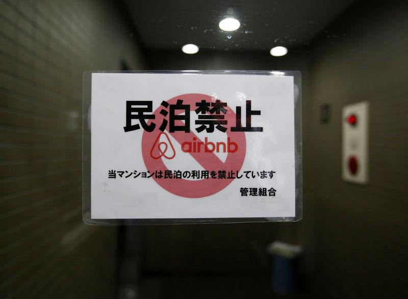A sign communicating the ban on using the apartment building as Airbnb service by the building management is attached to the building's front door in Tokyo, Japan