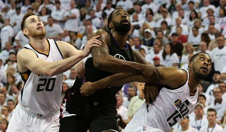Gordon Hayward (L) and Derrick Favors of the Utah Jazz try to block DeAndre Jordan of the Los Angeles Clippers in Game Three of the Western Conference Quarterfinals