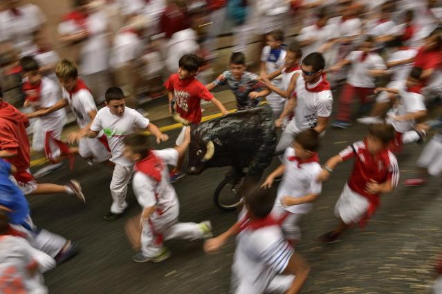 """<p>Boys run next to a toy bull imitating the running of the bull, during the """"Encierro Txiki"""", just for young runners, during the San Fermin Festival, in Pamplona, northern Spain, July 10, 2017. (AP Photo/Alvaro Barrientos) </p>"""