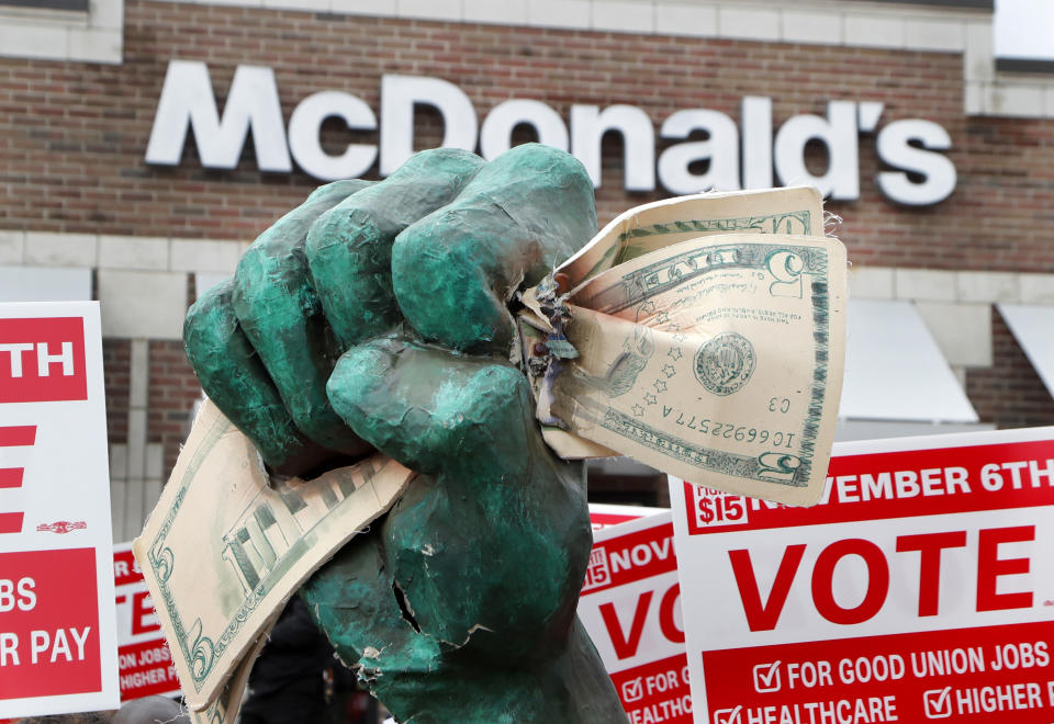 A protester holds up an oversize fist clenching fifteen dollars during a rally in front of a McDonald's restaurant Tuesday, Oct. 2, 2018, in Detroit. The group of protesters were calling for higher pay and the right to form unions in Michigan. (AP Photo/Carlos Osorio)