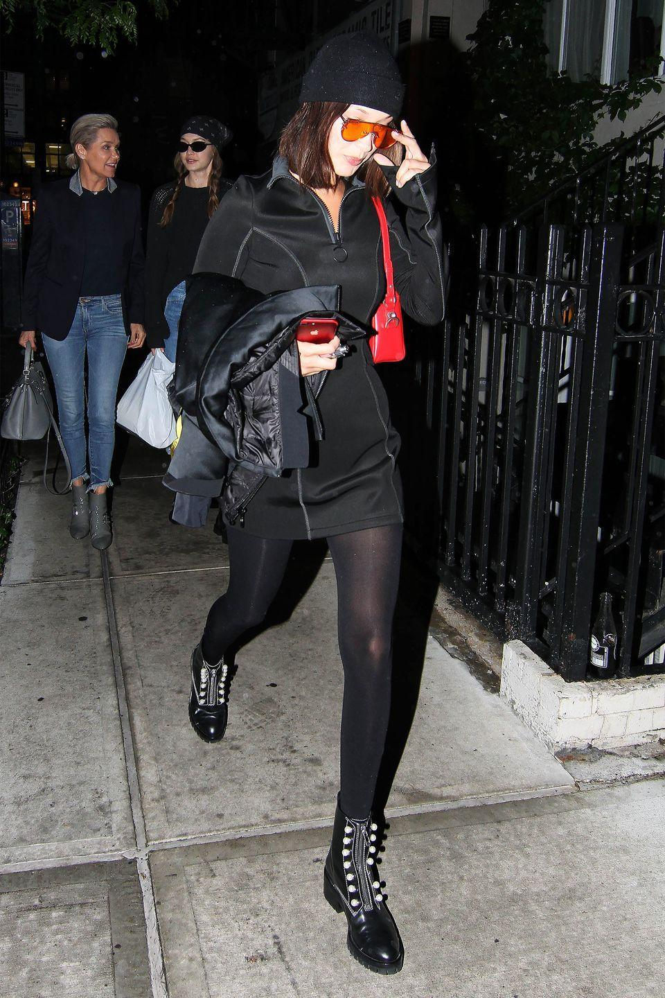 <p>In embellished combat boots, quarter zip dress, black tights, tinted aviator sunglasses and red bag while out in New York.</p>