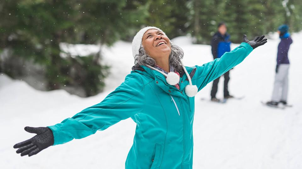 Beautiful ethnic woman in her 50s heads out for a snowshoeing adventure in the white forest with her husband and daughter, who are in the background.