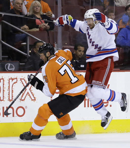 New York Rangers' Dominic Moore, right, collides with Philadelphia Flyers' Hal Gill during the first period of a preseason NHL hockey game, Tuesday, Sept. 17, 2013, in Philadelphia. (AP Photo/Matt Slocum)