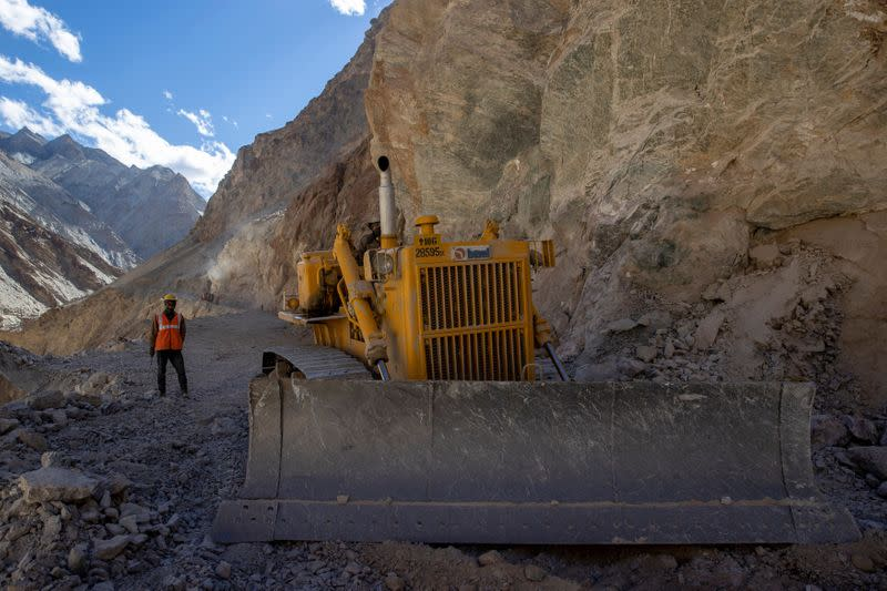 A Border Roads Organisation (BRO) worker operates a bulldozer on an under construction highway in the Ladakh region