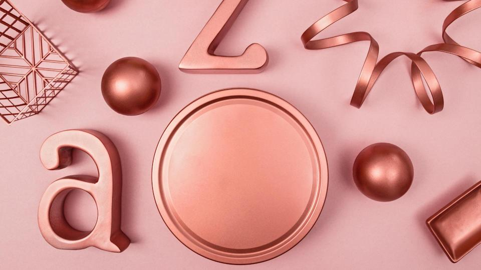 Decorative metal objects on pastel pink background.