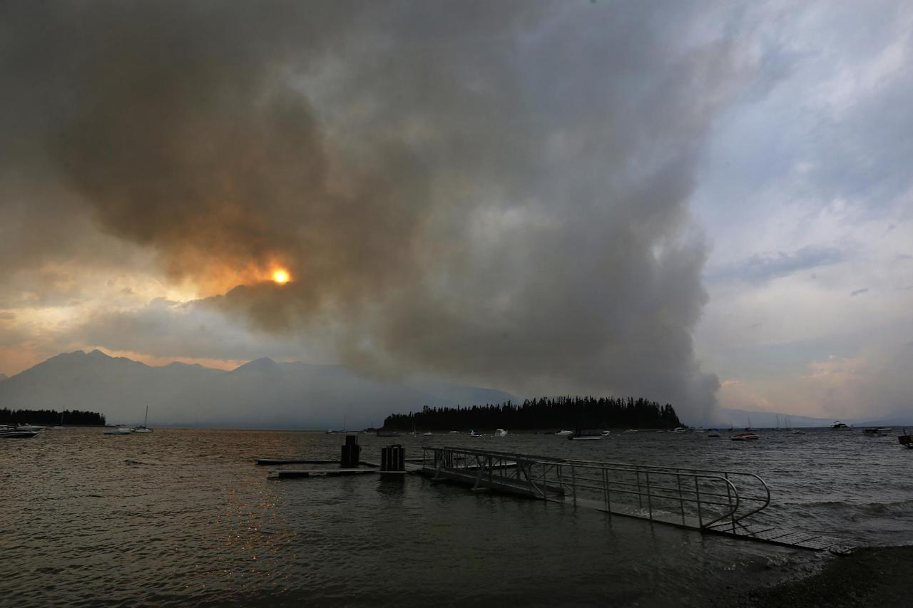A wildfire is visible from Leek's Marina on the shore of Jackson Lake, in north Grand Teton National Park, Wyo., Wednesday, Aug. 24, 2016. Some tourists heading to Yellowstone National Park during the busy summer season were facing an hourlong detour Wednesday as a wildfire in neighboring Grand Teton National Park kept a highway closed. Firefighters hope cooler weather slows the flames over the next couple of days. (AP Photo/Brennan Linsley)