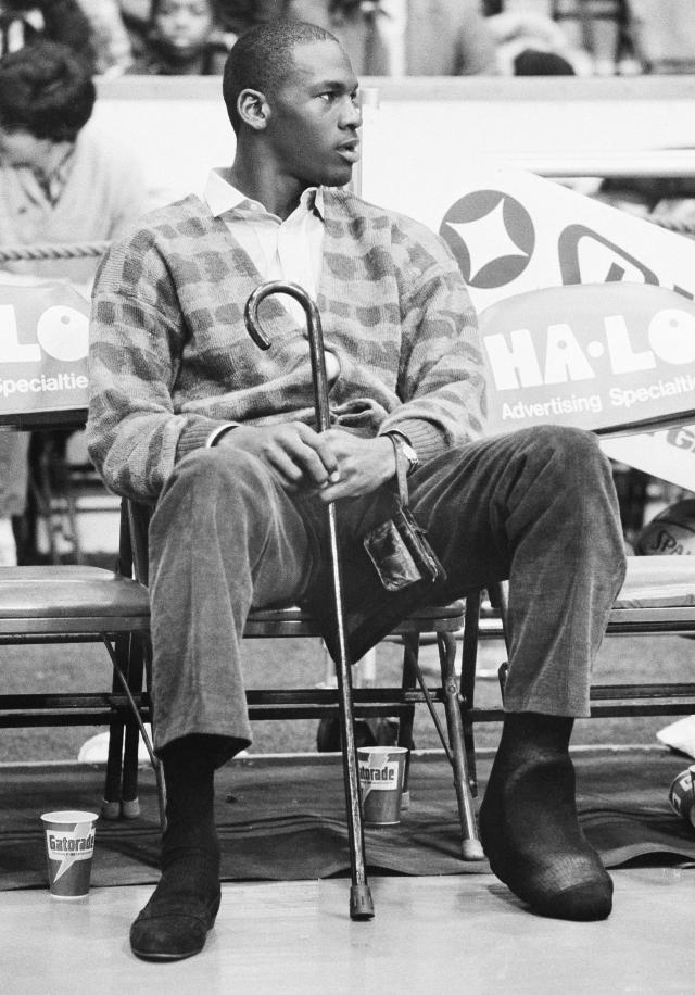 While nursing a foot injury, Michael Jordan sits on the bench while watching his Chicago Bulls play the New York Knicks in Chicago, on Dec. 26, 1985. (AP Photo/Fred Jewell)