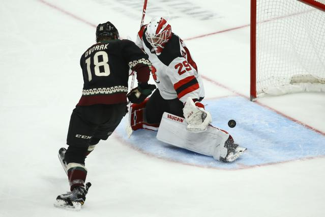 New Jersey Devils goaltender Mackenzie Blackwood (29) gets a pad on the puck on a shot from Arizona Coyotes center Christian Dvorak (18) during the third period of an NHL hockey game, Saturday, Dec. 14, 2019, in Glendale, Ariz. The Devils defeated the Coyotes 2-1. (AP Photo/Ross D. Franklin)