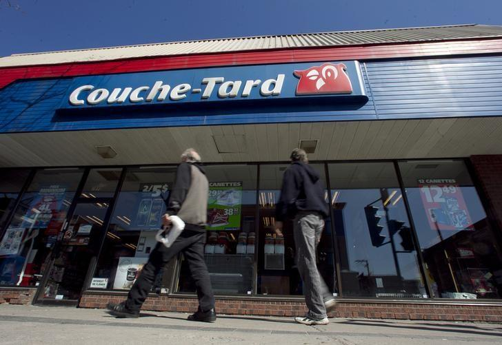 Pedestrians walk past a Couche-Tard convenience store in Montreal