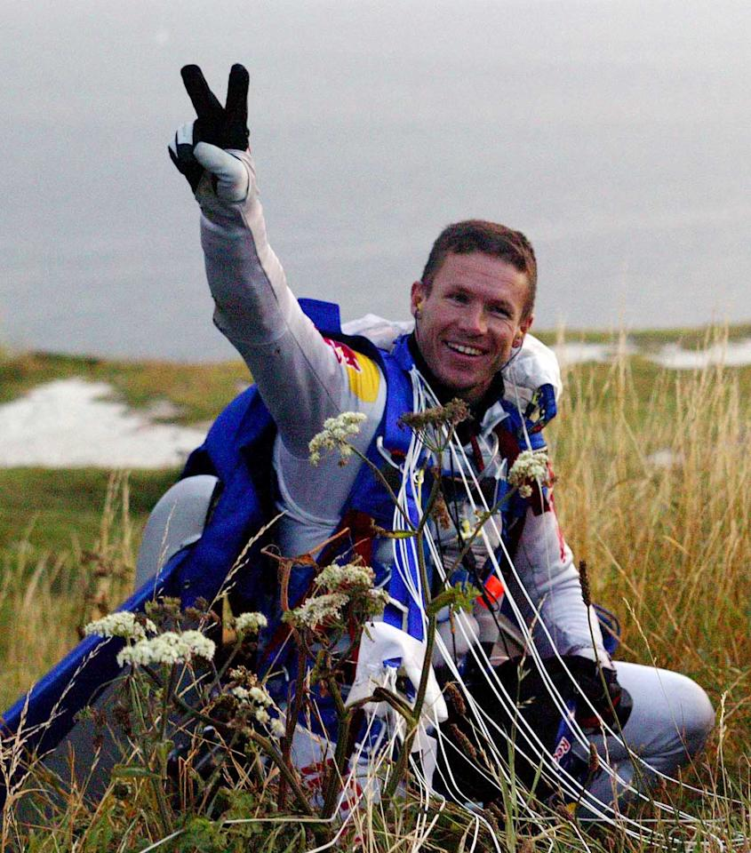 Austrian skydiver Felix Baumgartner celebrates after his successful freefall across the English Channel between Dover and Calais, July 31, 2003. After jumping out of a plane at 9000 metres (29,500ft) above Dover in southern England, wearing only an aerodynamic jumpsuit with a 6ft (1.8m) carbon fin strapped to his back, oxygen to breathe, and a parachute to land, Baumgartner landed safely in Calais after an eight-minute flight on Thursday, becoming the first person to skydive across the English Channel. REUTERS/Bernhard Spoettel