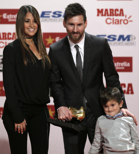 FILE In this Friday, Nov 24, 2017 filer, FC Barcelona's Lionel Messi poses with his wife Antonella Roccuzzo and their son Thiago after receiving his Golden Shoe award for leading all of Europe's leagues in scoring last season in Barcelona, Spain. Cristiano Ronaldo and Lionel Messi put up impressive numbers, in life and on the field, going into a fourth World Cup for each. So much has happened for football's standout stars since the 2014 tournament left both still lacking the game's most coveted prize.(AP Photo/Manu Fernandez, File)