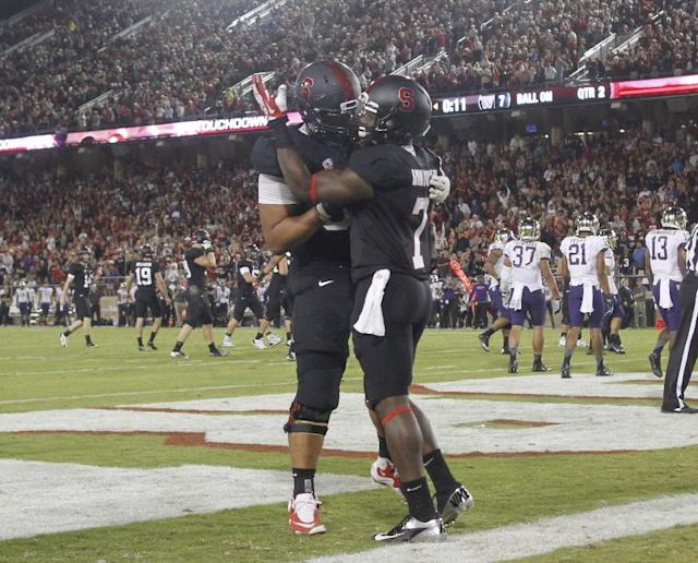 Stanford's Ty Montgomery, right, celebrates with teammate David Yankey after scoring a touchdown against Washington during the first half of an NCAA college football game in Stanford, Calif., Saturday, Oct. 5, 2013. (AP Photo/George Nikitin)