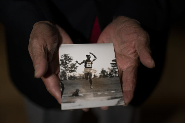 In this July 8, 2019, photo, Kazuo Oda, a son of Mikio Oda, who won Japan's first Olympic gold medal and Asia's first individual gold medal at the 1928 Amsterdam Olympics, poses for photos with a photo of his father during an interview with The Associated Press at Edo-Tokyo Museum in Tokyo. There was no podium ceremony back then. And the flag that was raised was brought to the Netherlands by the Japanese delegation. (AP Photo/Jae C. Hong)