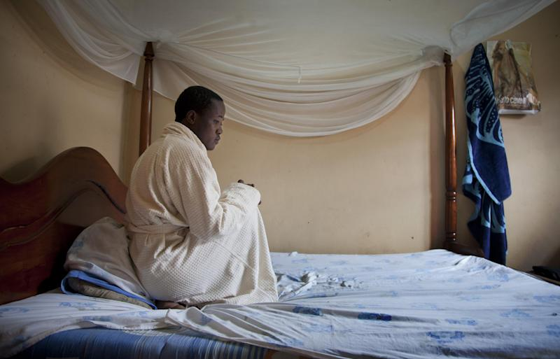 """In this photo taken Monday, March 24, 2014, a Ugandan homosexual sits on his bed in a safe-house which he shares with two roommates, at an undisclosed location in Uganda. The enactment of Uganda's new anti-gay law has spread fear among homosexuals, forcing many to flee to so-called """"safe houses"""", often single rooms that are more likely to be locked up day and night because of safety concerns. (AP Photo)"""
