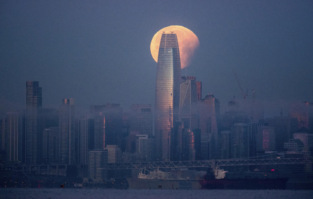 <p>A partially-eclipsed super blue blood moon sets behind the Salesforce Tower in San Francisco. It's the first time in 35 years a blue moon has synced up with a supermoon and a total lunar eclipse, also called a blood moon because of its red hue. (AP Photo/Noah Berger) </p>