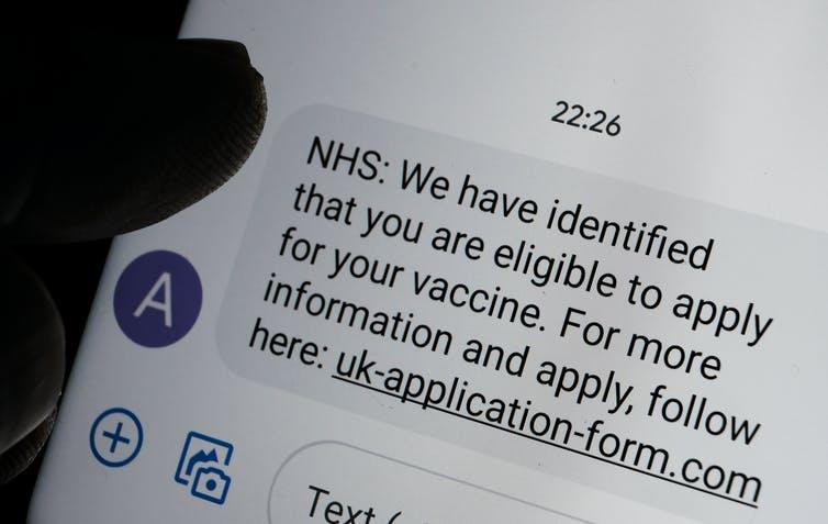 Scam COVID-19 vaccine text message seen on the smartphone screen and blurred silhouette of finger pointing at it.