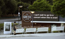 A walker passes by the still-closed Greek Theater concert venue, Tuesday, May 5, 2020, in the Los Feliz section of Los Angeles. Shutdown orders continue in California due to the coronavirus pandemic. (AP Photo/Chris Pizzello)