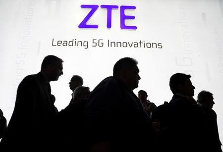 Visitors pass in front of the Chinese telecoms equipment group ZTE Corp booth at the Mobile World Congress in Barcelona, Spain, February 26, 2018. REUTERS/Sergio Perez