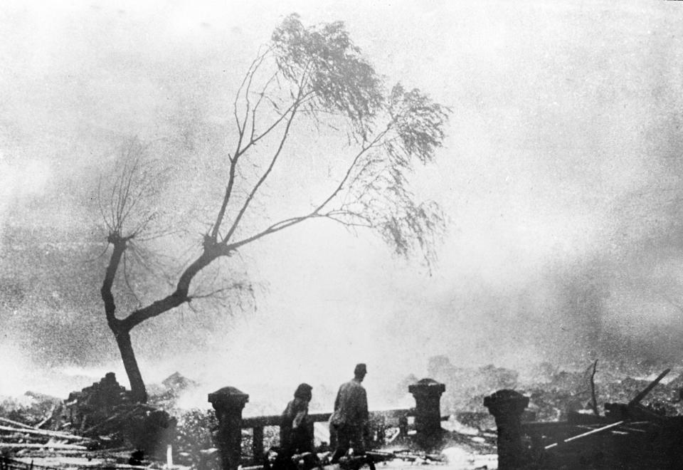 FILE - In this Aug. 9, 1945, file photo, survivors of the atomic bomb attack of Nagasaki, Japan, walk through the destruction as fire rages in the background. The city of Nagasaki in southern Japan marks the 75th anniversary of the U.S. atomic bombing of Aug. 9, 1945. It was a second nuclear bomb dropped by the U.S. three days after it made the world's first atomic attack on Hiroshima. Japan surrendered on Aug. 15, ending World War II and its nearly a half-century aggression toward Asian neighbors. Dwindling survivors, whose average age exceeds 83, increasingly worry about passing their lessons on to younger generations. (AP Photo, File)