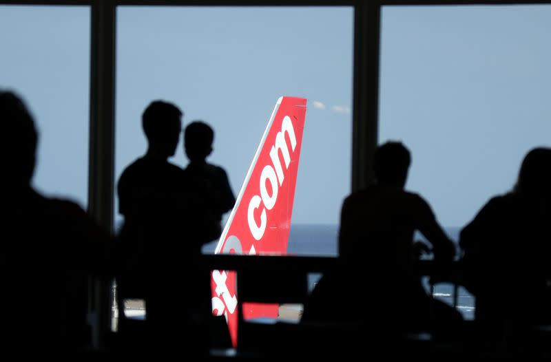 People look out at a Jet2.com aircraft from the departures area of Lanzarote Airport, in Lanzarote