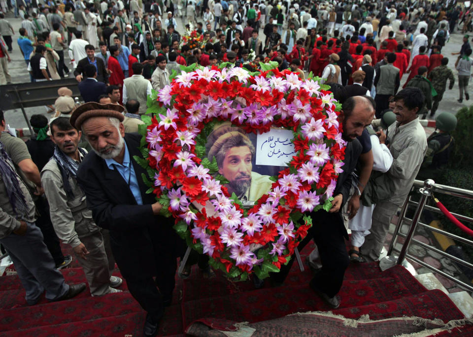 """FILE - In this Sept, 8, 2012 file photo, Afghans carry a wreath of flowers during a ceremony commemorating the 11th anniversary of the death of Ahmad Shah Massoud in Kabul, Afghanistan. The charismatic Northern Alliance commander was killed in an al-Qaida suicide bombing two days before the Sept. 11, 2001, attacks. Urdu writing on wreath reads, """"From the Gulam Haidar Khan High School."""" (AP Photo/Ahmad Jamshid, File)"""
