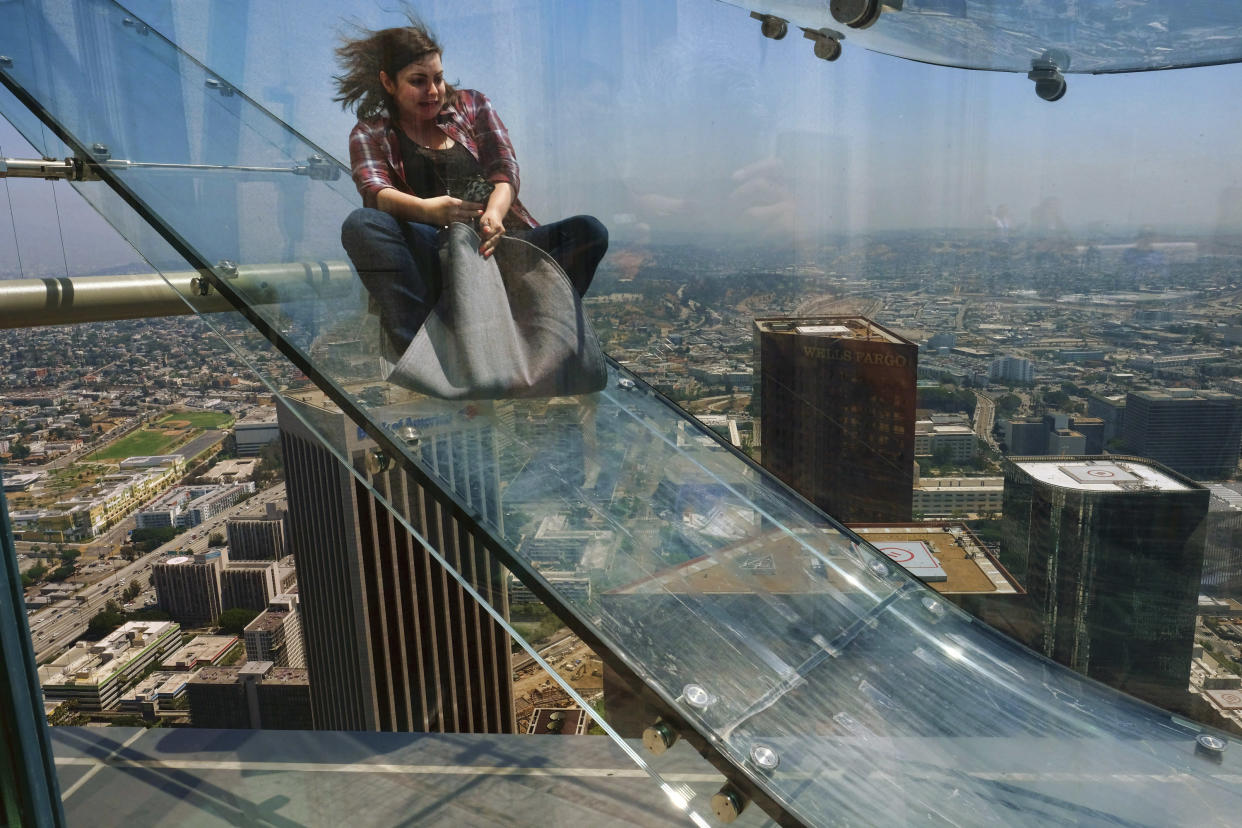 FILE - In this June 23, 2016, file photo, a member of the media rides down a glass slide during a media preview at the U.S. Bank Tower building in downtown Los Angeles. A renovation will do away with the Skyslide, located nearly a 1,000 feet high that gave thrill-seekers a brief ride on the outside of a downtown Los Angeles skyscraper. The new owner of the U.S. Bank Tower will remove the Skyslide and Skyspace public observation deck, the Los Angeles Times reported Friday, May 21, 2021. (AP Photo/Richard Vogel, File)