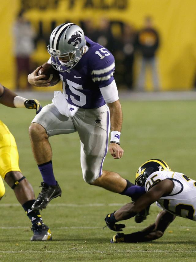 Kansas State's Jake Waters (15) is tripped by Michigan's Dymonte Thomas during the first half of the Buffalo Wild Wings Bowl NCAA college football game on Saturday, Dec. 28, 2013, in Tempe, Ariz. (AP Photo/Ross D. Franklin)