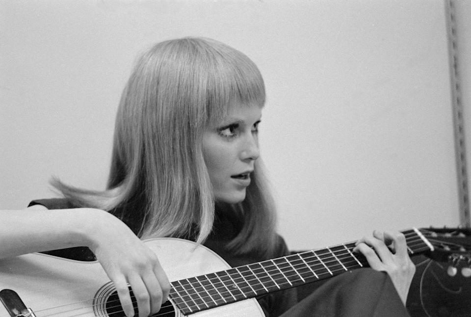 <p>Farrow plays around on the guitar, as she waits behind the scenes on the set of <em>John and Mary</em>, which was filmed in New York. </p>
