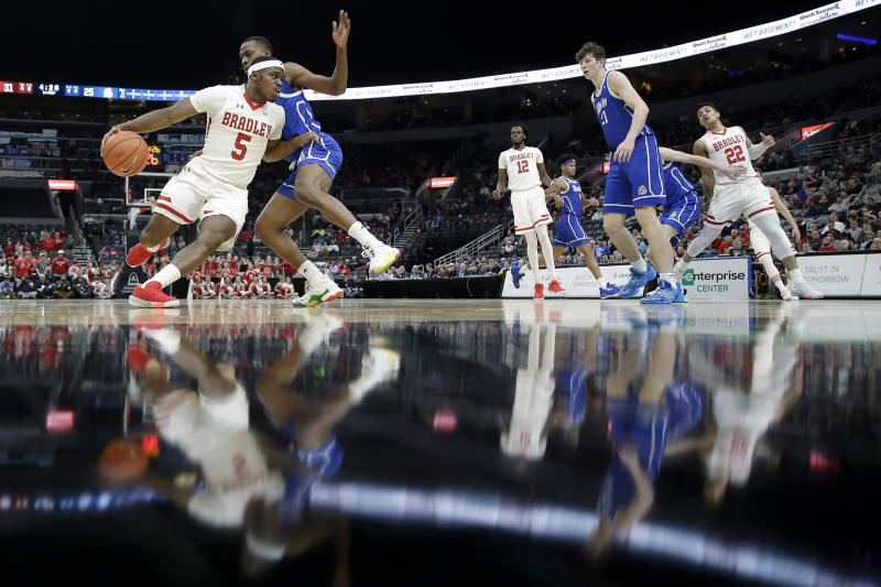 Bradley's Darrell Brown Jr. (5) heads to the basket past Drake's D.J. Wilkins during the first half of an NCAA college basketball game in the semifinal round of the Missouri Valley Conference men's tournament Saturday, March 7, 2020, in St. Louis. (AP Photo/Jeff Roberson)