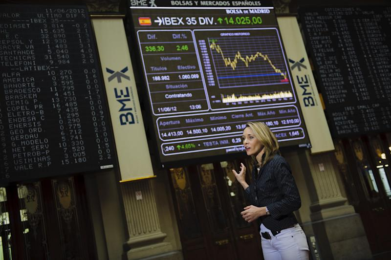 A journalist works in front of the Stock Exchange's main display while it shows Bankia values, in Madrid Monday June 11, 2012. After Spain's request for a European financial lifeline of up to a euro100 billion euros ($125 billion) to save its banks the EU made clear the money is more than just a loan. Besides being paid back with interest, there will be strings attached for the Spanish government.(AP Photo/Daniel Ochoa de Olza)