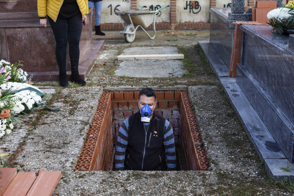 """FILE - In this Wednesday, April 1, 2020 file photo, an undertaker prepares a grave during the burial of Rosalia Mascaraque, 86, during the coronavirus outbreak in Zarza de Tajo, central Spain. After the European Union passed the death toll of half a million citizens lost to the coronavirus on Wednesday, Feb. 10, 2021, the EU Commission chief said that stalling rollout of the vaccines could be partly blamed on the bloc being over-optimistic, over-confident and plainly """"too late."""" (AP Photo/Bernat Armangue, File)"""