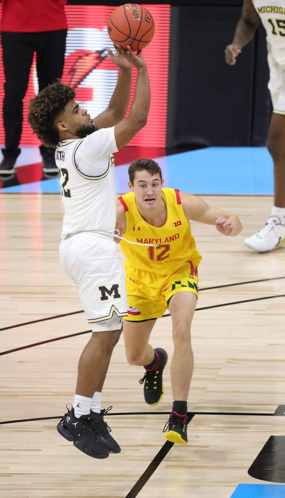 Mike Smith scores against Maryland's Reese Mona during Michigan's 79-66 win in the Big Ten tournament quarterfinals Friday, March 12, 2021 at Lucas Oil Stadium in Indianapolis.