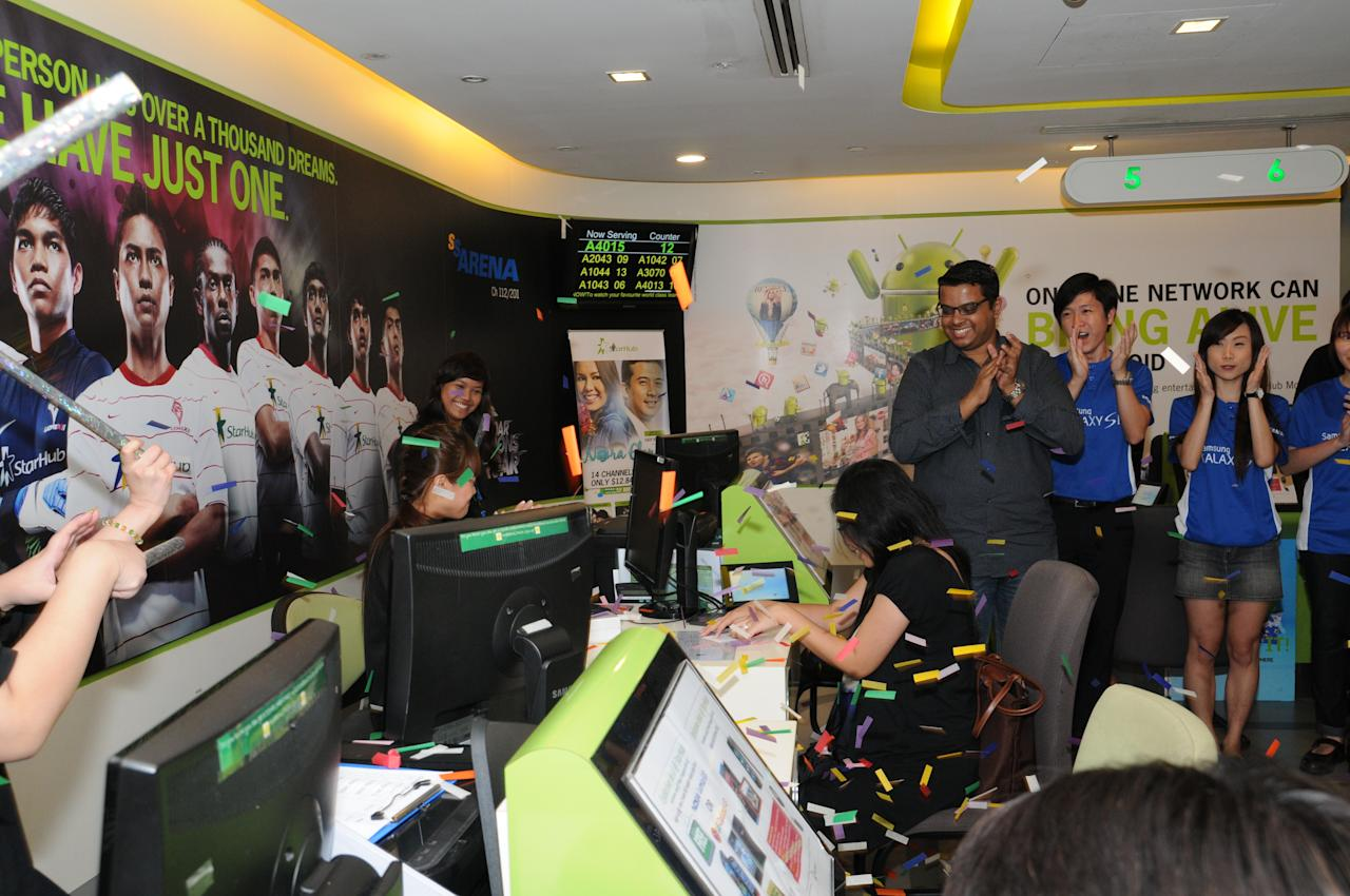 StarHub celebrates with one of the first customers on her purchase of the GALAXY S III at StarHub, Plaza Singapura