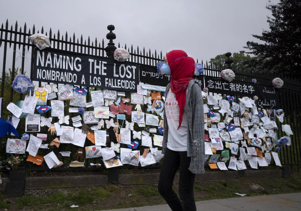 """A woman passes a fence outside Brooklyn's Green-Wood Cemetery adorned with tributes to victims of COVID-19, Thursday, May 28, 2020, in New York. The memorial is part of the Naming the Lost project which attempts to humanize the victims who are often just listed as statistics. The wall features banners that say """"Naming the Lost"""" in six languages: English, Spanish, Mandarin, Arabic, Yiddish and Bengali. (AP Photo/Mark Lennihan)"""