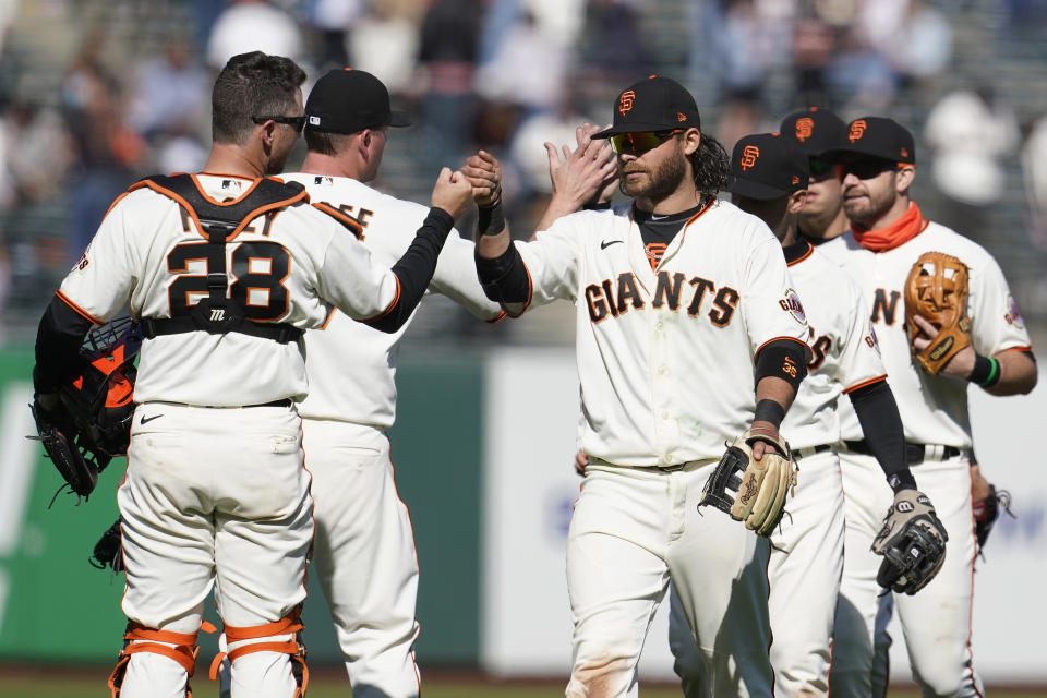 San Francisco Giants catcher Buster Posey (28) celebrates with shortstop Brandon Crawford, center right, and teammates after they defeated the Colorado Rockies in a baseball game in San Francisco, Saturday, April 10, 2021. (AP Photo/Jeff Chiu)