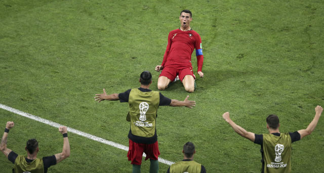 Portugal's Cristiano Ronaldo slides on his knees on the pitch as he celebrates after scoring his side's 2nd goal during the group B match between Portugal and Spain at the 2018 soccer World Cup in the Fisht Stadium in Sochi, Russia, Friday, June 15, 2018. (AP Photo/Thanassis Stavrakis)