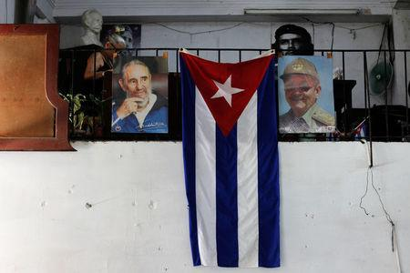The Cuban flag hangs next to the photographs of late Cuba's President Fidel Castro and his brother, Cuba's former President Raul Castro, in Havana, Cuba July 21, 2018. REUTERS/Stringer