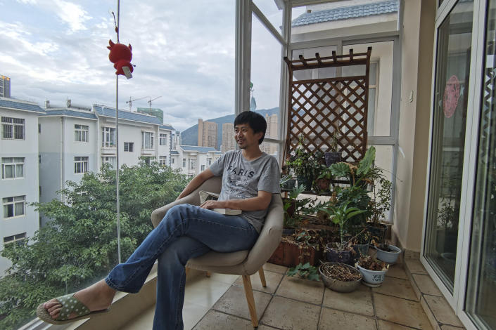 """In this photo released by Guo Jianlong, Guo sits at the balcony of his home in Dali in southwestern China's Yunnan province on June 29, 2021. Guo joined a small but visible handful of Chinese urban professionals who are rattling the ruling Communist Party by choosing to """"lie flat,"""" or reject grueling careers for what they call a """"low-desire life."""" That is clashing with the ruling party's message of success and consumerism as its celebrates the 100th anniversary of its 1921 founding. (Guo Jianlong via AP)"""