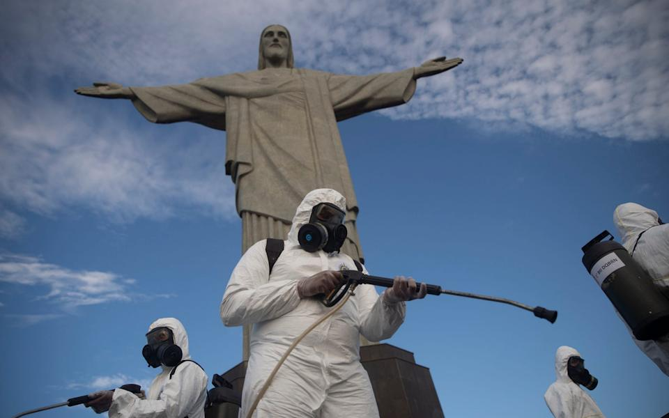 Soldiers disinfect the Christ the Redeemer site, currently closed, to prepare for what tourism officials hope will be a surge in visitors in the upcoming weekend as health restrictions are eased amid the new coronavirus pandemic in Rio de Janeiro, Brazil - Silvia Izquierdo/AP