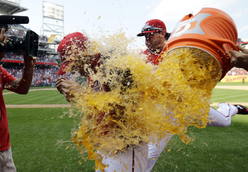 Washington Nationals starting pitcher Gio Gonzalez, center, is dunked with gatorade by relief pitcher Drew Storen, right, after a baseball game against the Milwaukee Brewers at Nationals Park Saturday, Sept. 22, 2012, in Washington. It was Gonzalez's 20th win of the season, and the Nationals won 10-4. (AP Photo/Alex Brandon)